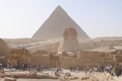Unrecognizable distant travelers walking on old path near ancient Sphinx statue and Great Pyramid of Giza located in Egypt on sunny day