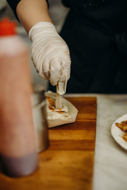 Person Pouring White Cream on Brown Wooden Table