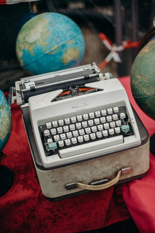 Green and Gray Typewriter on Red Table