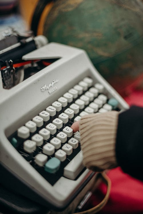 Person Holding Gray and Black Typewriter