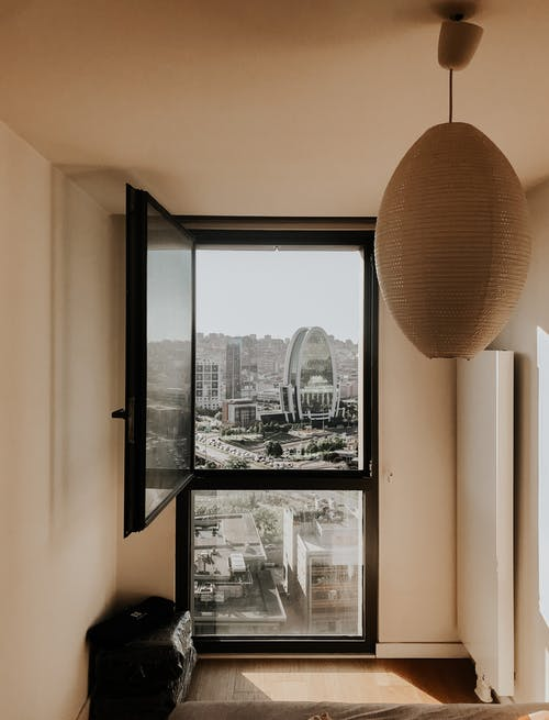 Minimalist stylish interior of cozy room with amazing city view from window on sunny day
