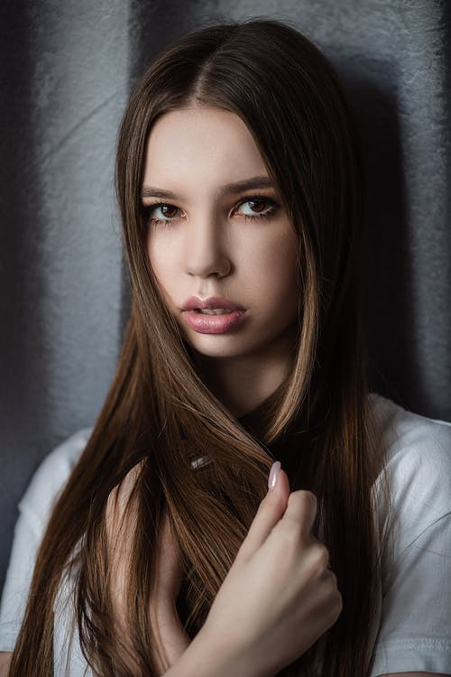Gorgeous young female looking at camera while touching long straight hair and leaning on gray wall