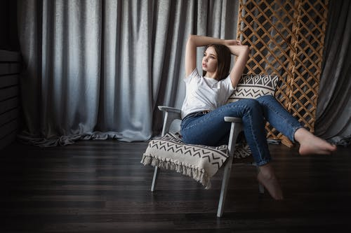 Young slim woman relaxing on armchair and looking away