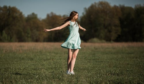 Happy young female with long hair in dress spinning around on grassy meadow in countryside