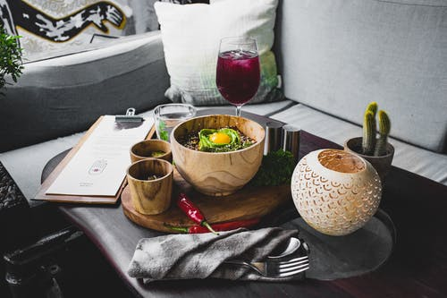 Serving of oriental food in wooden dishes with drinks on table of modern cafe