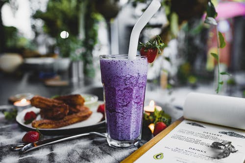 Glass of lavender dessert placed on table near menu