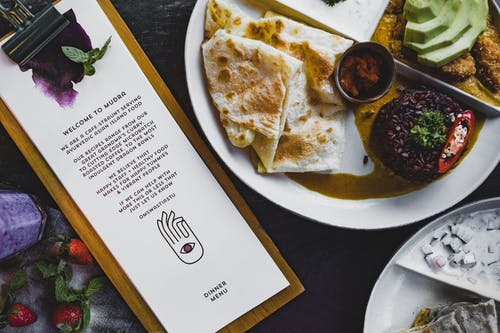 Asian island food on plate placed on table with welcome page of  cafe menu