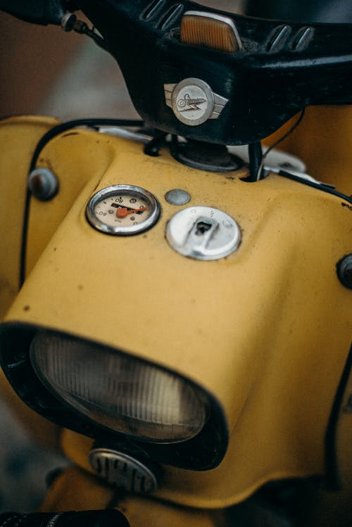 Yellow and Black Motorcycle With White and Black Round Buttons