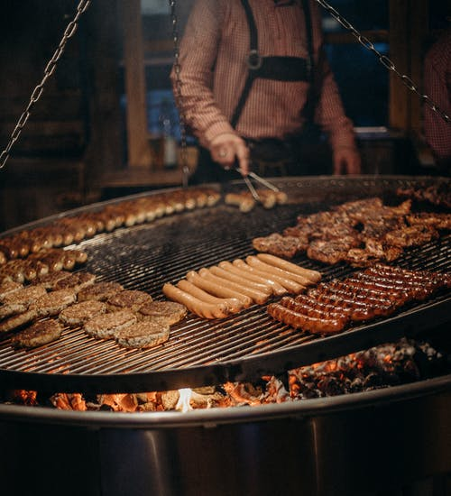 Person Cooking Meat on Grill