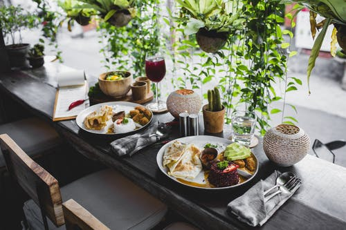 High angle of plates with assorted healthy dishes served on wooden table with cutlery and drinks in stylish tropical cafe
