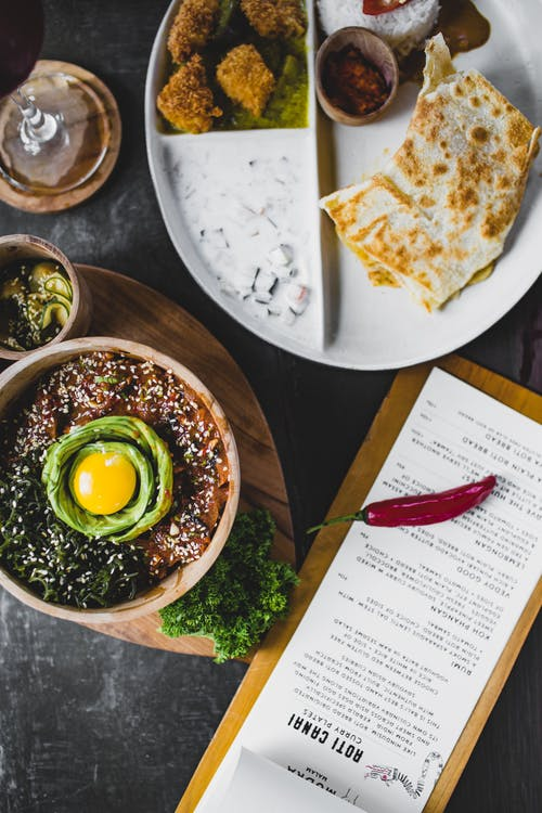 Top view of miso bowl with egg placed on table near menu and plate with various sauces and garnishes in exotic restaurant