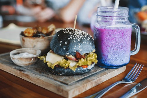 Delicious hamburger and mug of cold smoothie on wooden board