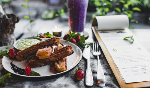 Crispy sweet churros served with sauce and strawberries and placed on table near menu and fresh blueberry smoothie