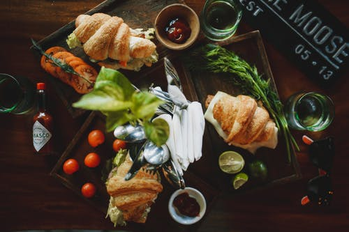 Set of appetizing croissant sandwiches on table in cafe