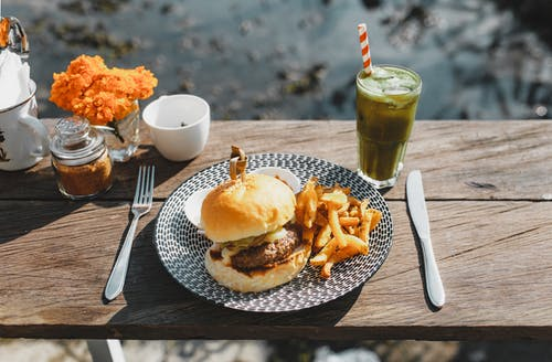 Plate with appetizing hamburger and french fries placed on lumber table near glass of green drink in outdoor cafe