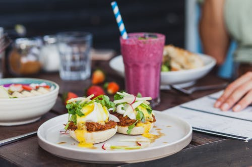 Appetizing sandwiches with poached eggs and sauce served with berry smoothie and placed on table with crop unrecognizable woman reading menu on background
