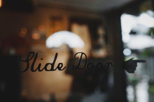 Slide door inscription on glass entrance of modern cafe against blurred interior during daytime