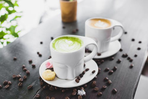 Cups of cappuccino and matcha tea served on cafe terrace