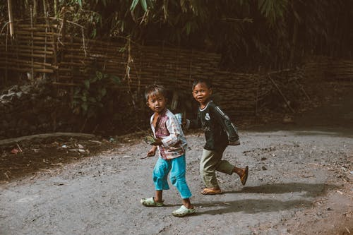Full body of little ethnic children walking on dirty path near green plants in village on sunny day