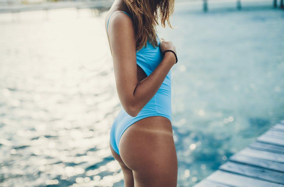 Crop fit woman enjoying sunny day on pier near sea