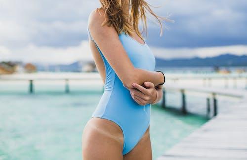 Crop slender lady in swimwear standing on berth near sea