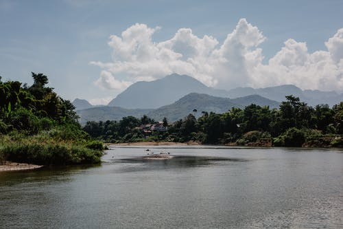 Amazing landscape of calm lake surrounded by tropical forest and high mountain ranges under beautiful cloudy sky