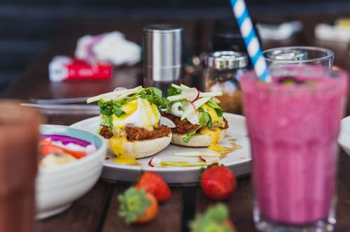 Tasty breakfast with poached eggs and glass of fruit drink