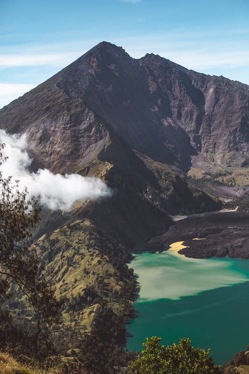 Breathtaking landscape of Rinjani active volcano and crater lake surrounded by rough formations on sunny day