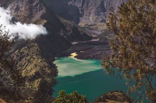 Crater lake between volcanic mountains on sunny day