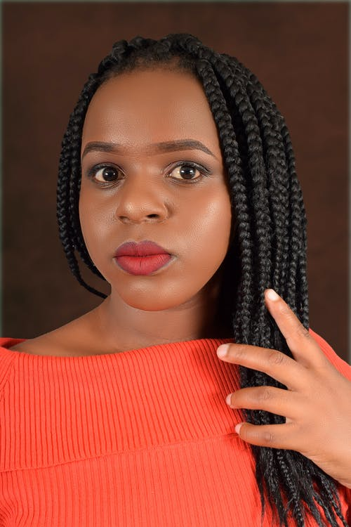 Confident young African American female in casual clothes touching braided hair and looking at camera against brown background
