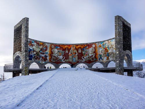 Low angle of old stone arched Russia Georgia Friendship Monument with tile mural inside located on snowy hill in Gudauri