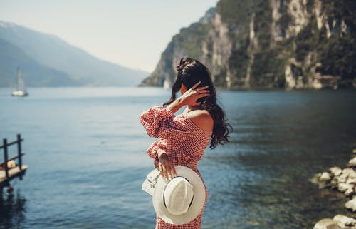 Stylish woman admiring seascape and cliff