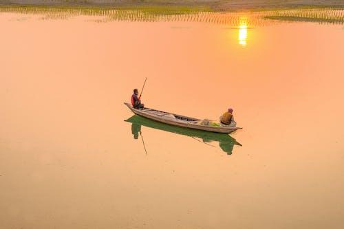 Anonymous fishermen in boat at sundown