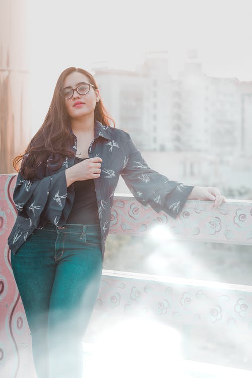 Stylish young ethnic lady relaxing on terrace