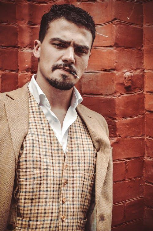 Elegant young brutal man smoking near brick wall