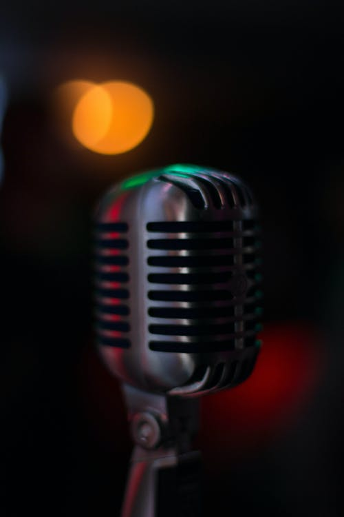 Contemporary silver microphone standing on stage in dark room against blurred background with illuminated lamp during music creation in evening