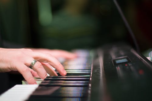 Anonymous musician playing electric piano in room