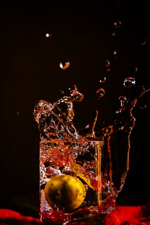 Glass with splashing water and small fruit inside against black background in dark room in modern studio with drops of drink