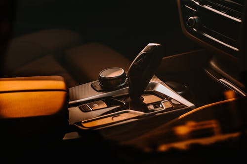 Interior of expensive vehicle with black lever on automatic transmission placed near sound system in modern automobile in dark evening