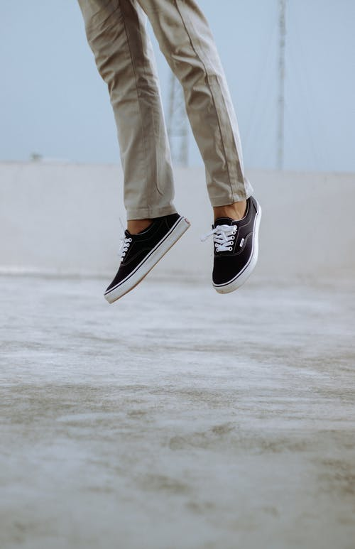 Crop person jumping on pavement
