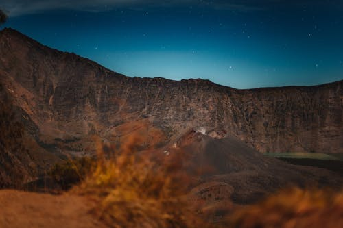 Breathtaking view of majestic Rinjani volcano located amidst rocky mountain ridge against starry night sky