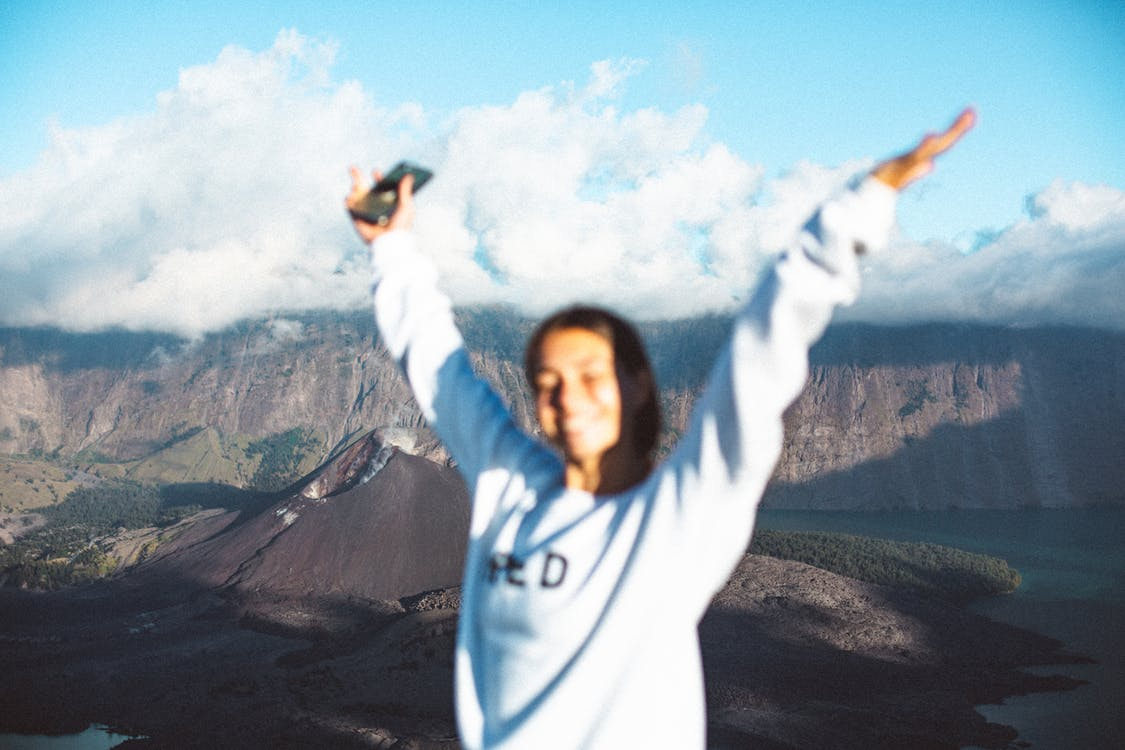 Delighted woman against Rinjani volcano