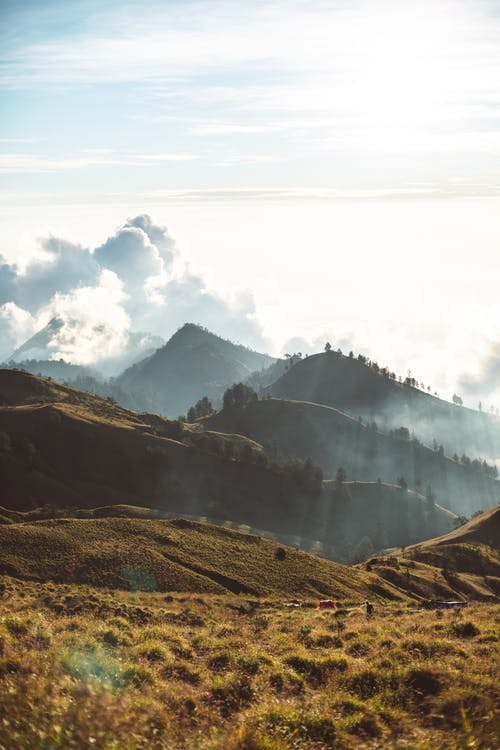 Hilly terrain on cloudy day at sunrise