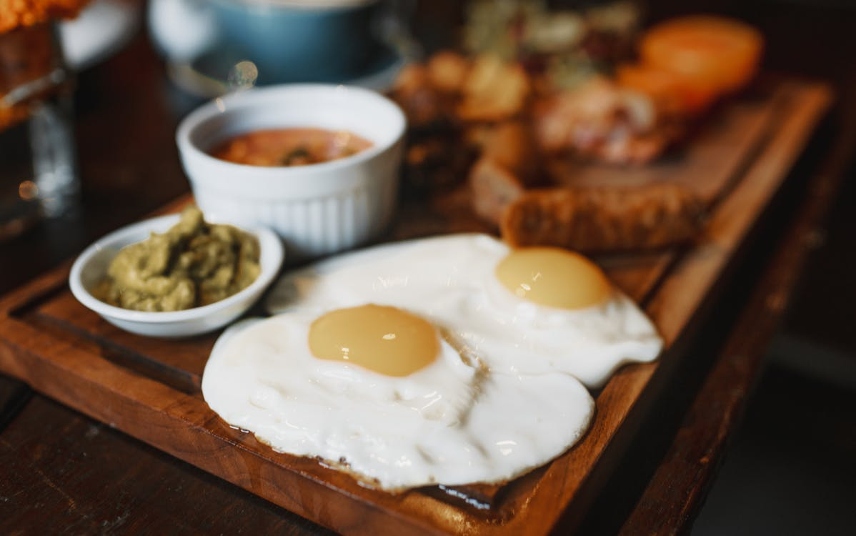 Satisfying breakfast of tasty fried eggs and different delicious appetizers served on wooden stand on table