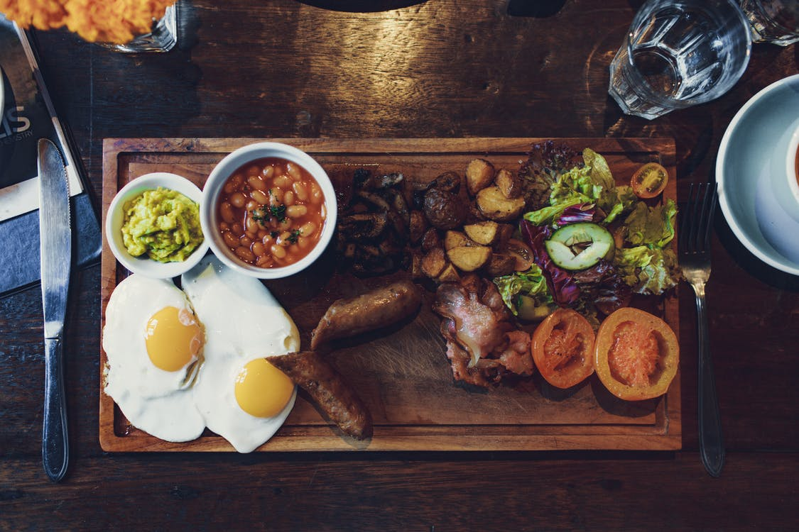 Top view of delicious fried eggs and vegetables with sausages and beans on wooden tray with fork and knife
