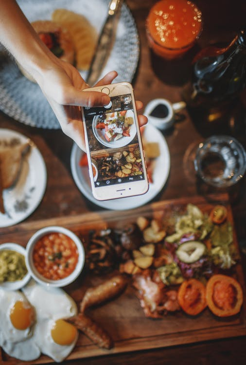 Crop person taking photo of delicious breakfast