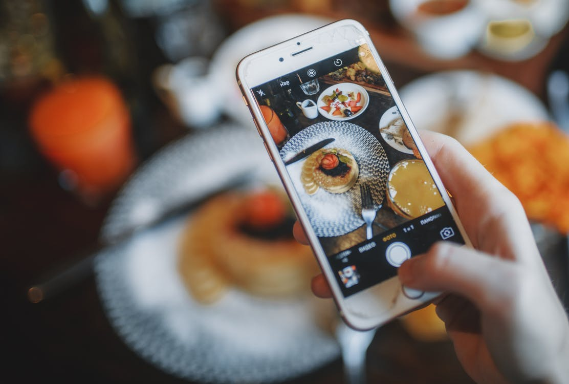 Crop person taking photo of food on smartphone of food