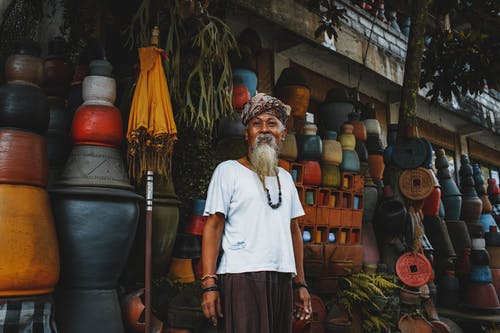 Ethnic old man standing on street market
