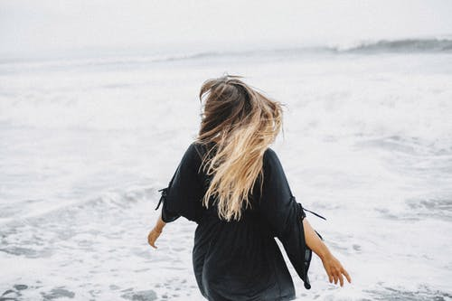 Anonymous woman walking near waving sea
