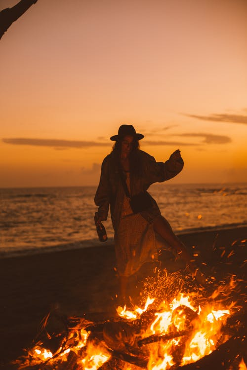 Young woman standing near fire and sea
